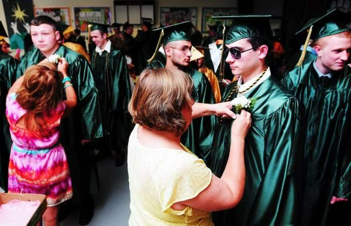 Arnold Gold Ñ Register Vickie Brai (center) pins a carnation on Casey Redfield (right) for graduation ceremonies at Emmett O'Brien Technical High School in Ansonia on 6/21/2013.