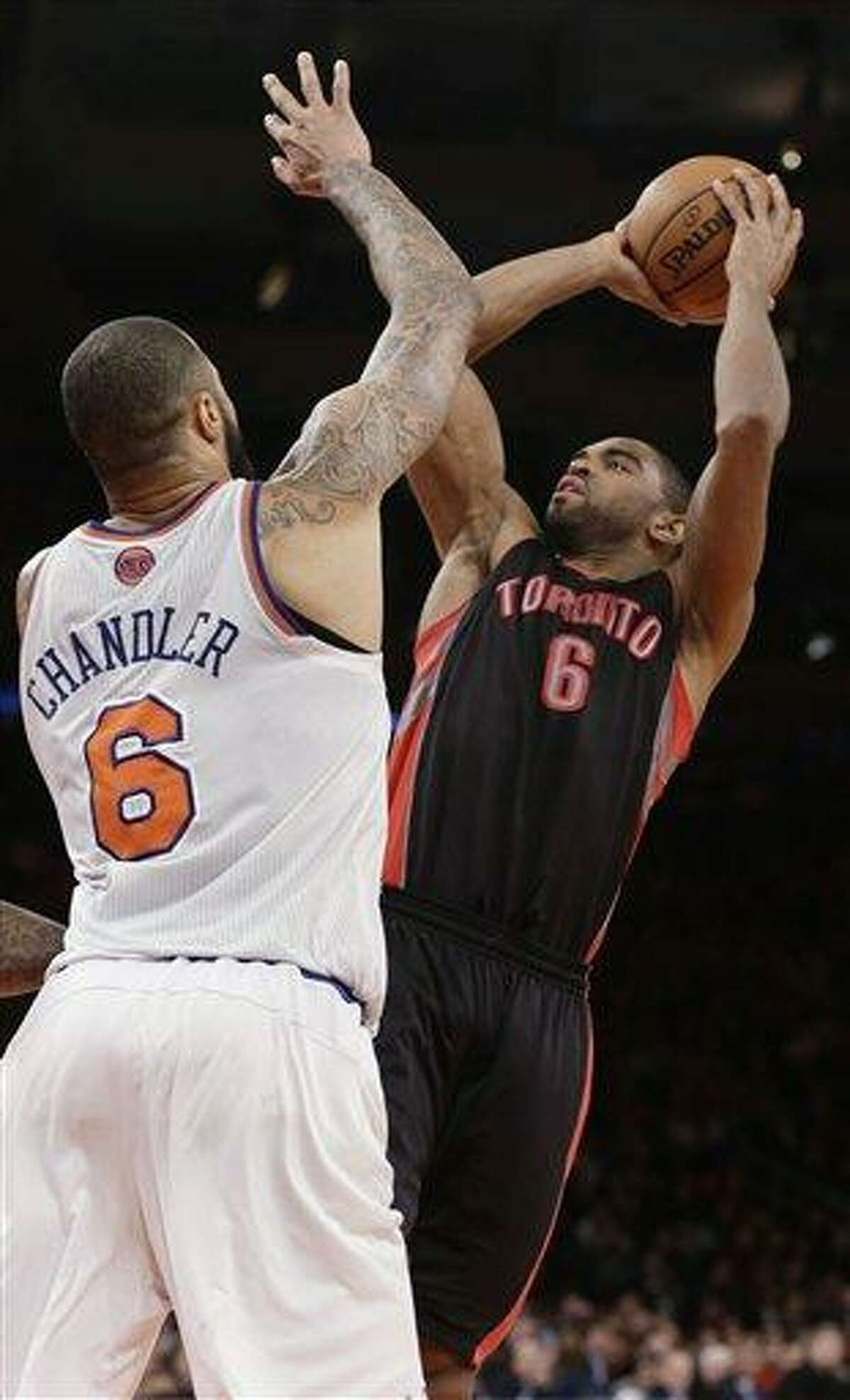 Toronto Raptors' Alan Anderson (6) shoots over New York Knicks' Tyson Chandler (6) during the second half of an NBA basketball game Wednesday, Feb. 13, 2013, in New York. Anderson scored 26 points as the Raptors won 92-88. (AP Photo/Frank Franklin II)