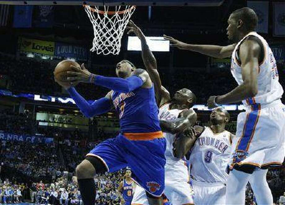 New York Knicks forward Carmelo Anthony (7) shoots in front of Oklahoma City Thunder center Kendrick Perkins (5) in the third quarter of an NBA game in Oklahoma City, April 7, 2013. Photo: AP / AP