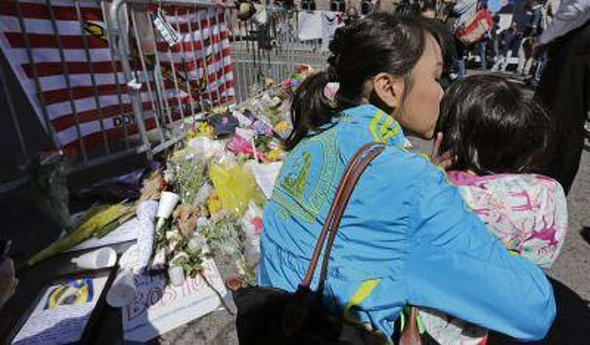 Boston Marathon runner Vu Trang, of San Francisco, kisses her two-year-old daughter Cara at a makeshift memorial on Boylston Street near the finish line of Monday's Boston Marathon explosions, which killed at least three and injured more than 140, in Boston, Wednesday, April 17, 2013. The bombs that blew up seconds apart near the finish line left the streets spattered with blood and glass, and gaping questions of who chose to attack at the Boston Marathon and why. (AP Photo/Charles Krupa)