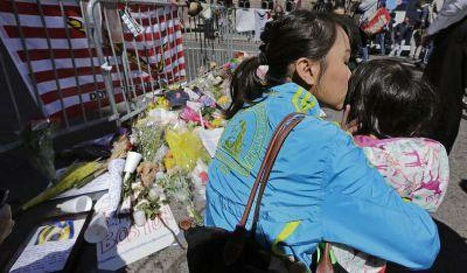 Boston Marathon runner Vu Trang, of San Francisco, kisses her two-year-old daughter Cara at a makeshift memorial on Boylston Street near the finish line of Monday's Boston Marathon explosions, which killed at least three and injured more than 140, in Boston, Wednesday, April 17, 2013. The bombs that blew up seconds apart near the finish line left the streets spattered with blood and glass, and gaping questions of who chose to attack at the Boston Marathon and why. (AP Photo/Charles Krupa) Photo: AP / AP