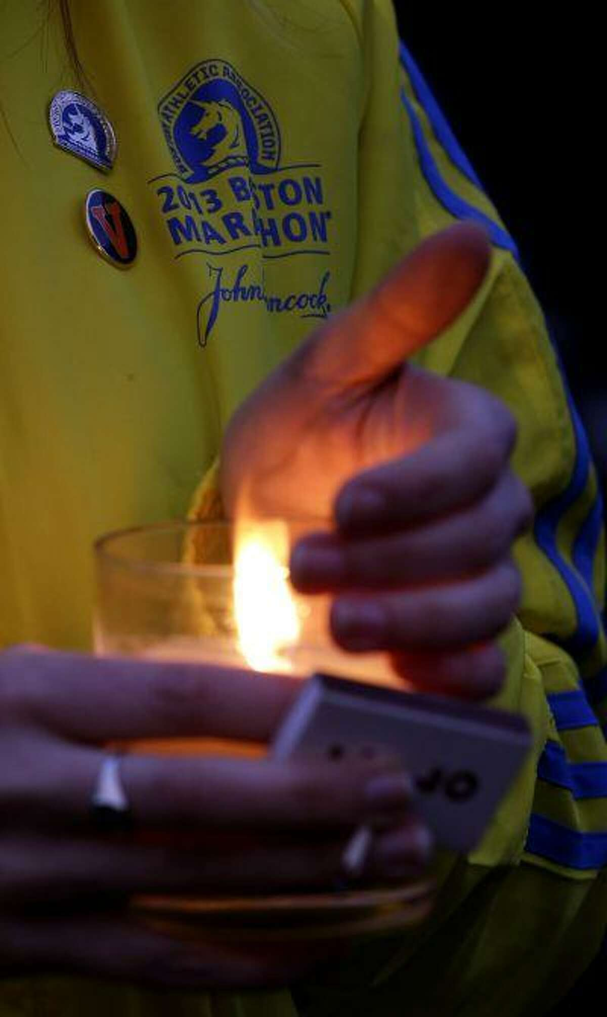 Lauren Jones, 30, of Boston, who volunteered during the Boston Marathon and was three blocks from the site of the explosions, holds a candle during a vigil for the victims at Boston Common, Tuesday, April 16, 2013. (AP Photo/Julio Cortez)
