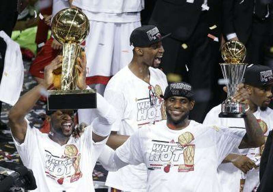 The Miami Heat's Dwyane Wade, left, holds the Larry O'Brien NBA Championship Trophy as LeBron James holds his Bill Russell NBA Finals Most Valuable Player Award after Game 7 of the NBA basketball championship against the San Antonio Spurs, Friday, June 21, 2013, in Miami. The Miami Heat defeated the San Antonio Spurs 95-88 to win their second straight NBA championship. The Miami Heat's Chris Bosh celebrates in the background. Photo: ASSOCIATED PRESS / AP2013