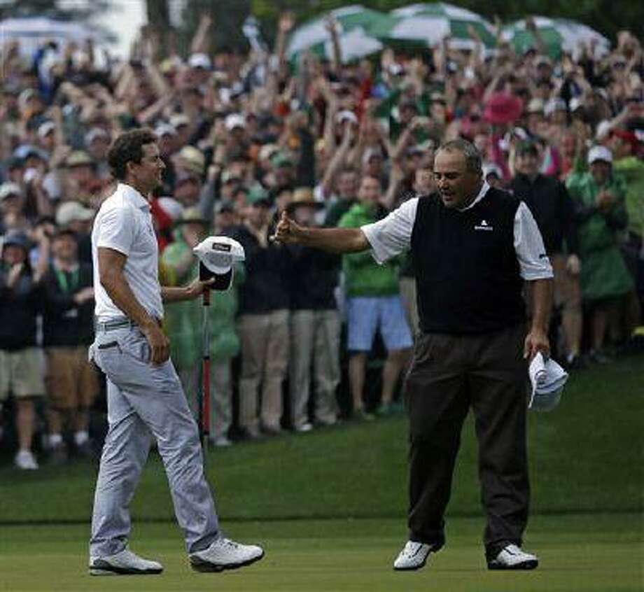 Angel Cabrera, of Argentina, gives Adam Scott, of Australia, a thumbs up after Scott made a birdie putt on the second playoff hole to win the Masters, April 14, 2013, in Augusta, Ga. Photo: AP / AP