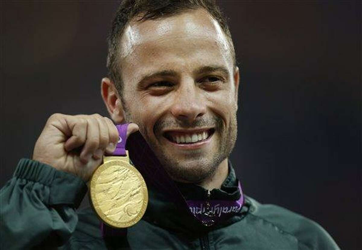 FILE - In this Saturday, Sept. 8, 2012, file photo, Gold medalist South Africa's Oscar Pistorius poses with his medal during the ceremony after winning the men's 400 meters T44 category final during the athletics competition at the 2012 Paralympics, in London. Olympic sprinter Oscar Pistorius has been arrested after a 30-year-old woman was shot dead at his home in South Africa. Police say Pistorius, a double-amputee known as
