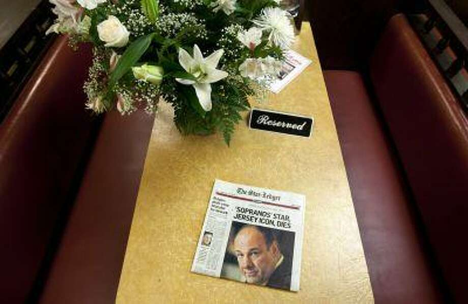 """A newspaper and bouquet of flowers adorn a booth in Holsten's Ice Cream Shop, which was the location of the final scene where the TV show """"The Sopranos"""" was filmed, in Bloomfield, New Jersey, June 20, 2013. Doctors at a Rome hospital battled for 40 minutes to try to save the life of James Gandolfini, 51, best known for his Emmy-winning role as a mob boss in the TV series """"The Sopranos,"""" before pronouncing him dead, the emergency room chief said on Thursday. (REUTERS/Carlo Allegri) Photo: REUTERS / X02452"""