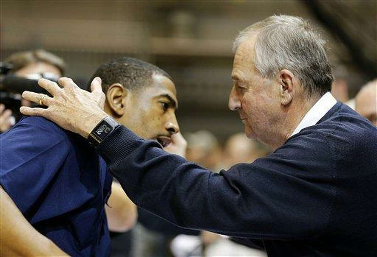 Jim Calhoun, former coach of Connecticut, right, hugs current head coach Kevin Ollie, left, after an NCAA men's basketball game against Michigan State on Saturday, Nov. 10, 2012, on the Ramstein U.S. Air Force Base, in Ramstein, Germany. (AP Photo/Michael Probst)