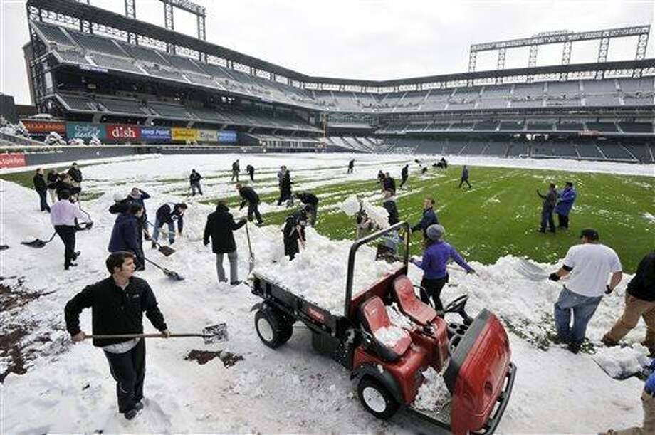 Coors Field grounds crew and stadium employees shovel snow before the start of a baseball doubleheader between the New York Mets and Colorado Rockies on Tuesday, April 16, 2013, in Denver. (AP Photo/Jack Dempsey) Photo: AP / FR42408 AP