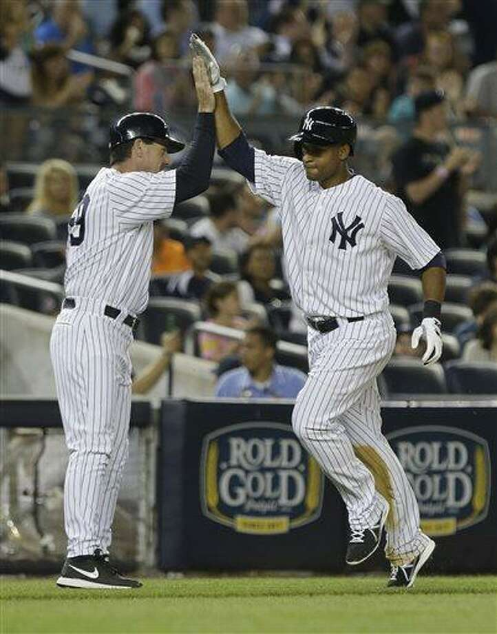 New York Yankees' Zoilo Almonte, right, celebrates with third base coach Rob Thomson as he heads to home plate after hitting a home run during the sixth inning of a baseball game on Friday, June 21, 2013, in New York. (AP Photo/Frank Franklin II) Photo: AP / AP