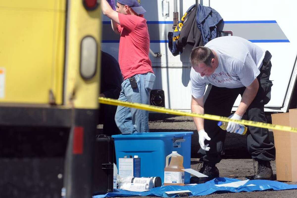 Law enforcement official examines items removed from a Mini Max Space Self Storage trailer at 445 Front Rd in West Haven as part of a West Haven police investigation of an alleged drug lab at the site. April 17, 2013. vm Williams
