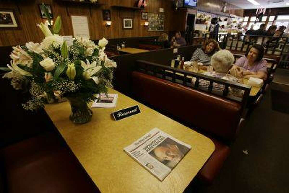 A reserved sign and flowers are seen on a table at Holsten's ice cream parlor Thursday, June 20, 2013, in Bloomfield, N.J., with a newspaper announcing the death of actor James Gandolfini. Gandolfini was mourned in the northern New Jersey towns where his TV character Tony Soprano lived, loved and whacked people. The star died Wednesday night in Italy of an apparent heart attack. (AP Photo/Mel Evans)
