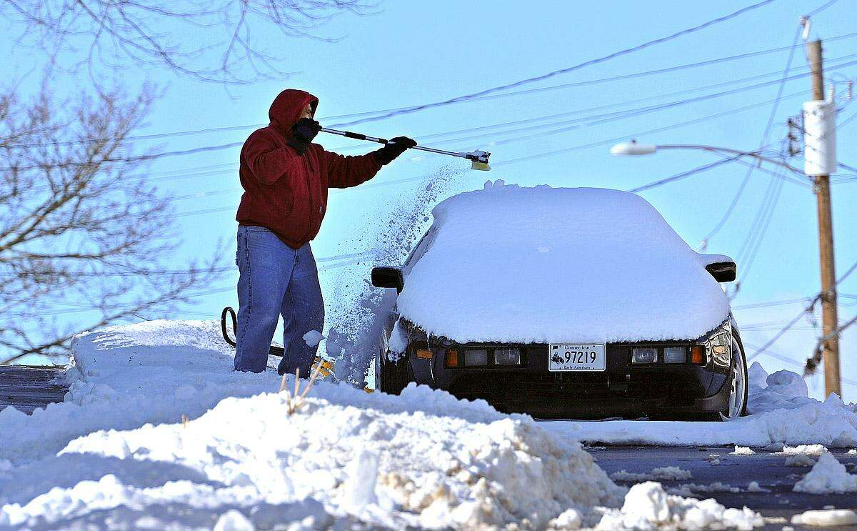 West Haven-- Hernan Fiallos clears off his classic Porshe along Arlington Street in West Haven Sunday morning. Photo-Peter Casolino 12/30/12 , West Haven-- Hernan Fiallos clears off his classic Porshe along Arlington Street in West Haven Sunday morning. Photo-Peter Casolino