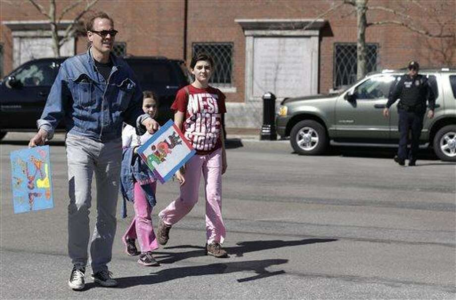 A man walks with children outside the John Joseph Moakley Federal Courthouse, which was evacuated with a code red, Wednesday, April 17, 2013, amid conflicting reports that a suspect in the deadly Boston Marathon bombing is in custody, in Boston. The FBI and the U.S. attorney's office in Boston say no arrests have been made in Monday's bombing, in Boston.  (AP Photo/Julio Cortez) Photo: AP / AP