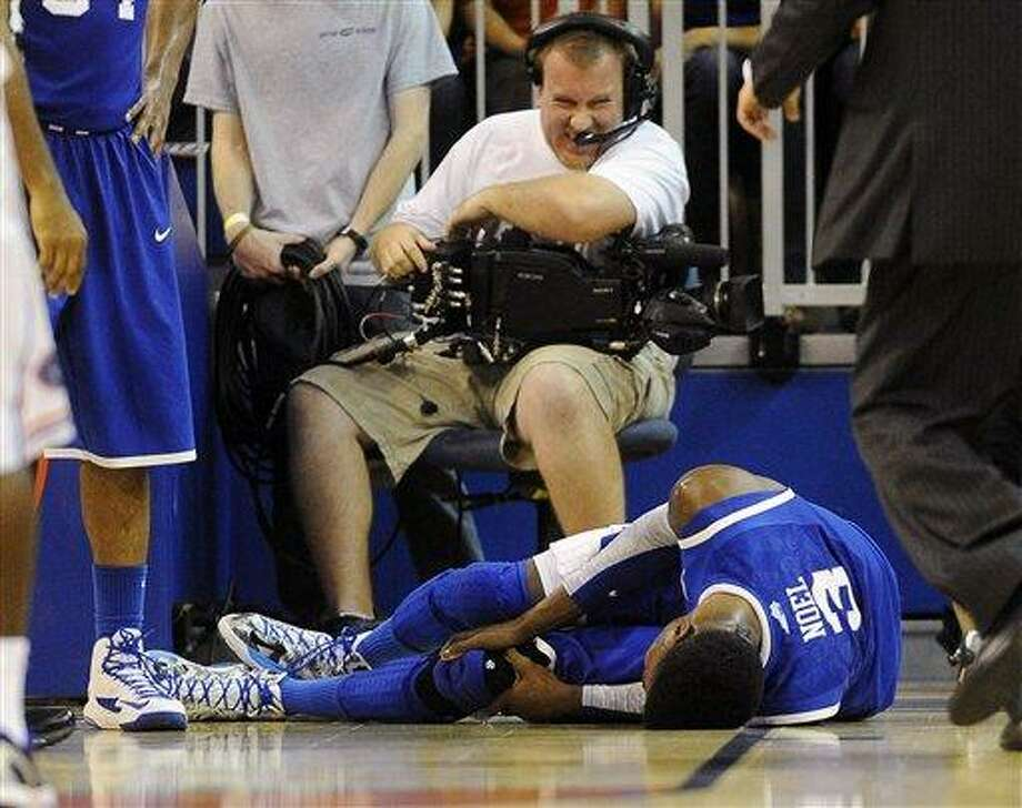 A cameraman grimmaces after a collision with Kentucky forward Nerlens Noel (3) during the second half of an NCAA college basketball game against Florida in Gainesville, Fla., Tuesday, Feb. 12, 2013. Noel injured his left knee and did not return. Florida won 69-52. (AP Photo/Phil Sandlin) Photo: ASSOCIATED PRESS / AP2013