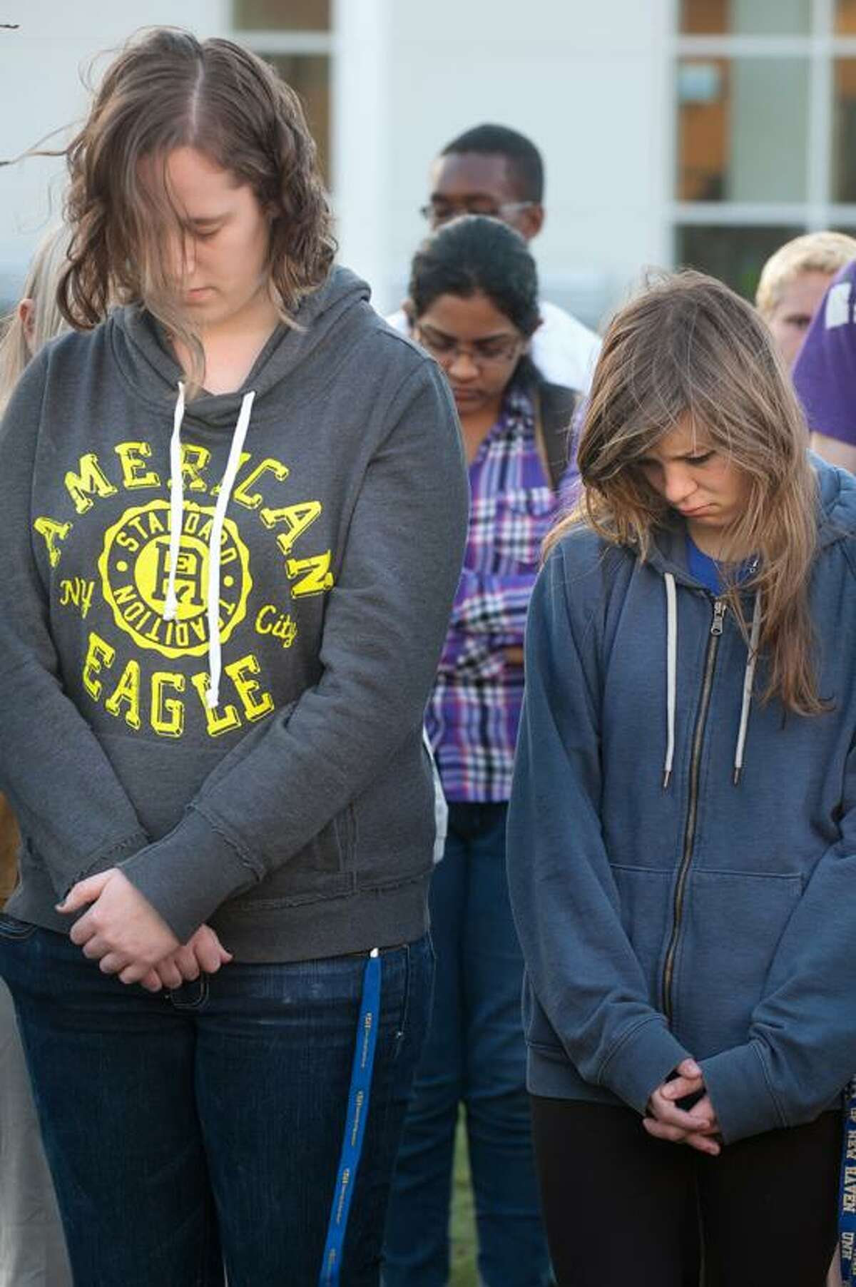 Alaina Kaiser, a sophomore and Marija Savaiko, a freshmen observe a moment of silence during a student vigil at UNH to remember those affected by the events of the Boston Marathon explosions April 17, 2013. vm Williams
