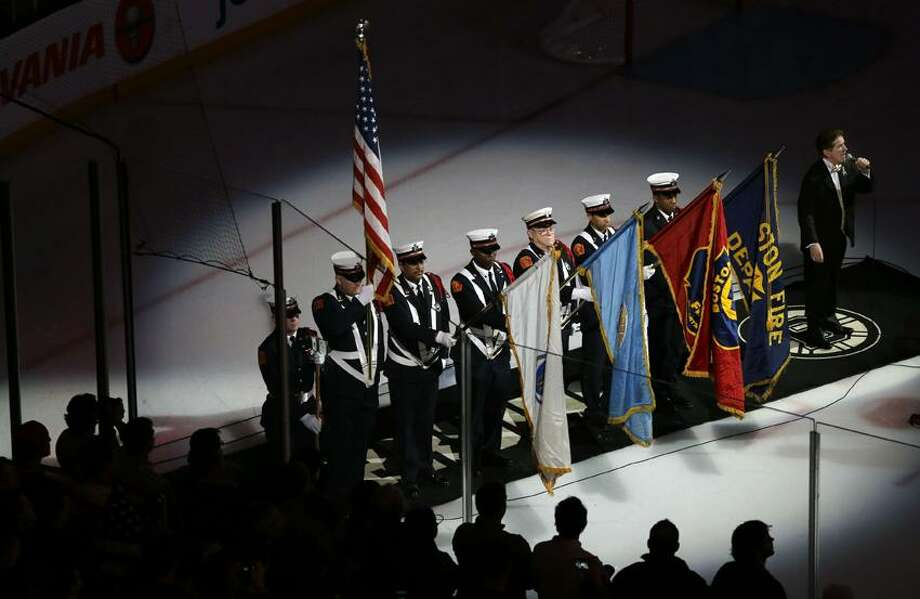 Members of a Boston Fire Department honor guard hold flags during the singing of the national anthem at TD Garden in Boston, Wednesday, April 17, 2013, during a pregame ceremony in the aftermath of Monday's Boston Marathon bombings. (AP Photo/Elise Amendola) Photo: AP / AP