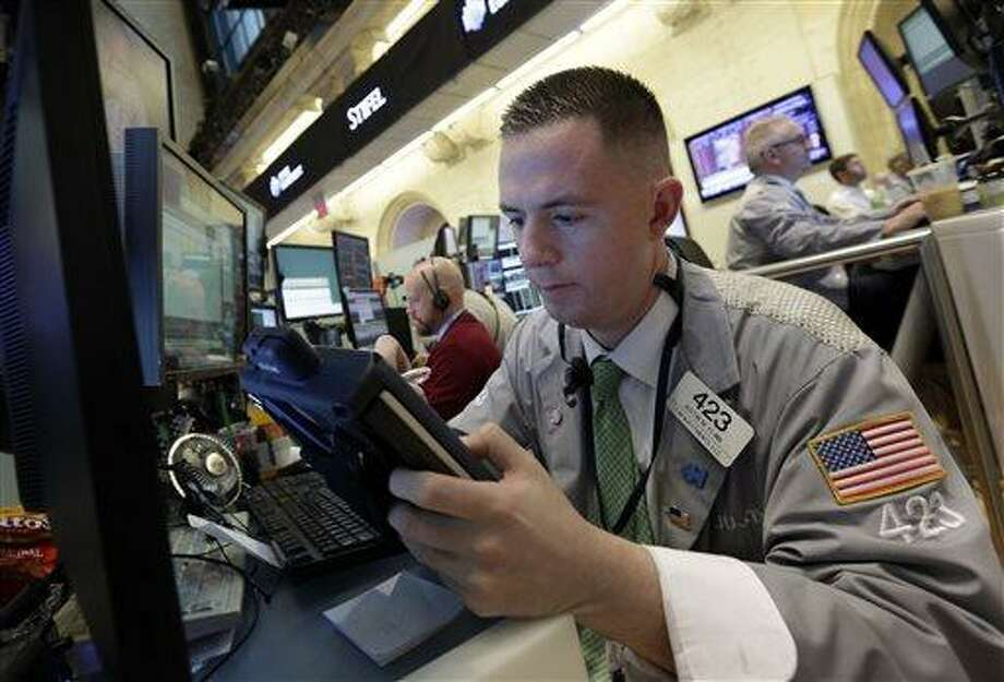 Trader Justin Flinn works in a booth on the floor of the New York Stock Exchange, Thursday, June 20, 2013. Financial markets are sliding after the Federal Reserve said it could end its huge bond-buying program by the middle of next year. (AP Photo/Richard Drew) Photo: AP / AP
