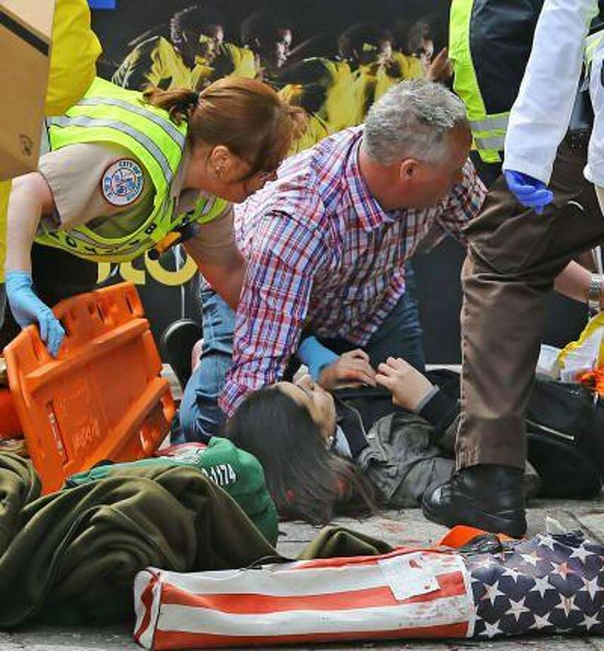 An emergency responder and passerby tend to Sydney Corcoran, a Lowell High School student who was injured by shrapnel in Monday's bomb explosion at the Boston Marathon.