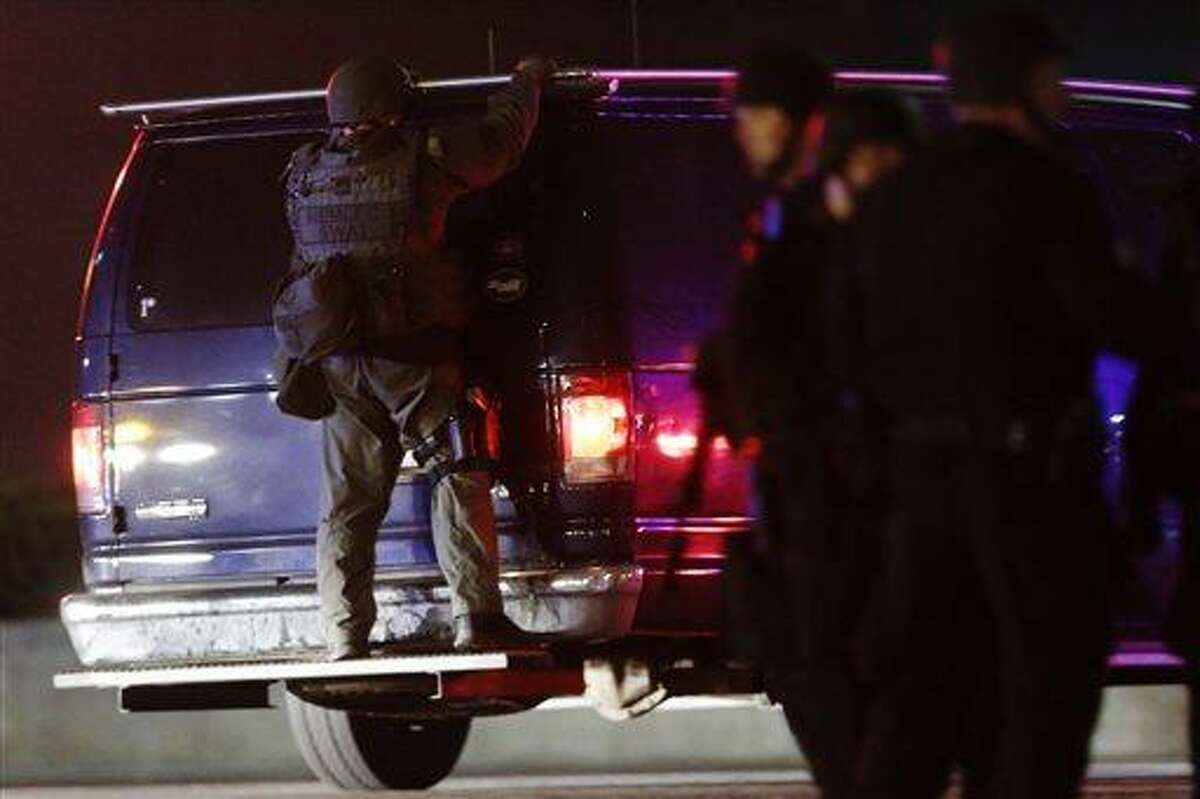 A police officers rides on the back of a van at a staging area as a manhunt is conducted for a suspect Friday, April 19, 2013, in Watertown, Mass. One of two suspects in the Boston Marathon bombing is dead and a massive manhunt is underway for another, authorities said early Friday April 19, 2013. Residents of Watertown, a Boston suburb, have been advised to keep their doors locked and not let anyone in. (AP Photo/Matt Rourke)
