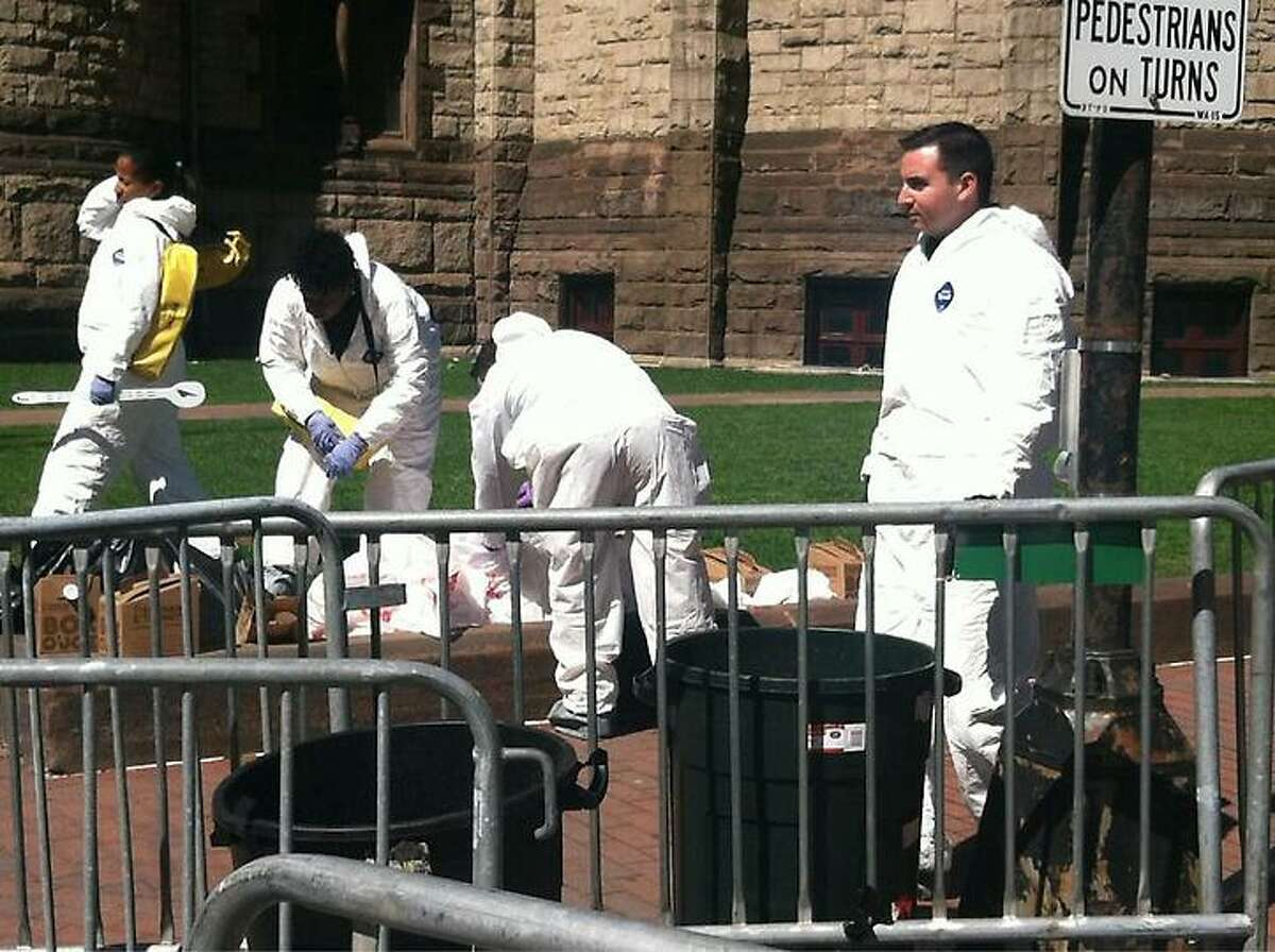 Workers in white suits carefully pick through leftovers from the race Wednesday. Jennifer Swift/Register