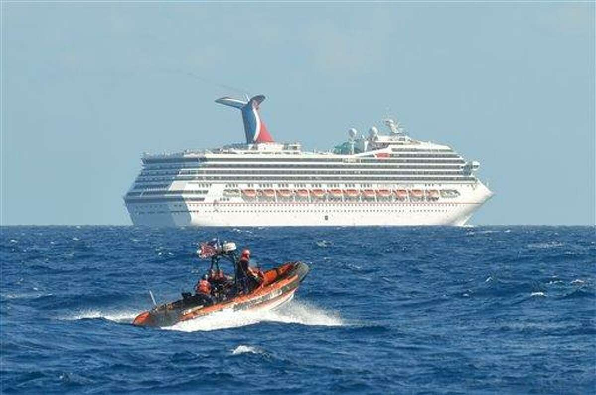 In this image released by the U.S. Coast Guard on Feb. 11, 2013, a small boat belonging to the Coast Guard Cutter Vigorous patrols near the cruise ship Carnival Triumph in the Gulf of Mexico, Feb. 11, 2013. The Carnival Triumph has been floating aimlessly about 150 miles off the Yucatan Peninsula since a fire erupted in the aft engine room early Sunday, knocking out the ship's propulsion system. No one was injured and the fire was extinguished. (AP Photo/U.S. Coast Guard- Lt. Cmdr. Paul McConnell