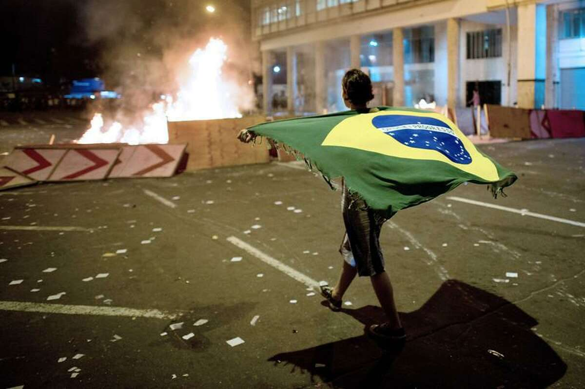 A demonstrator walks with a Brazilian flag late on June 19, 2013 in the center of Niteroi, 10 kms from Rio de Janeiro. Protesters battled police late on June 19, even after Brazil's two biggest cities rolled back the transit fare hikes that triggered two weeks of nationwide protests. The fare rollback in Sao Paulo and Rio de Janeiro marked a major victory for the protests, which are the biggest Brazil has seen in two decades. CHRISTOPHE SIMON/AFP/Getty Images