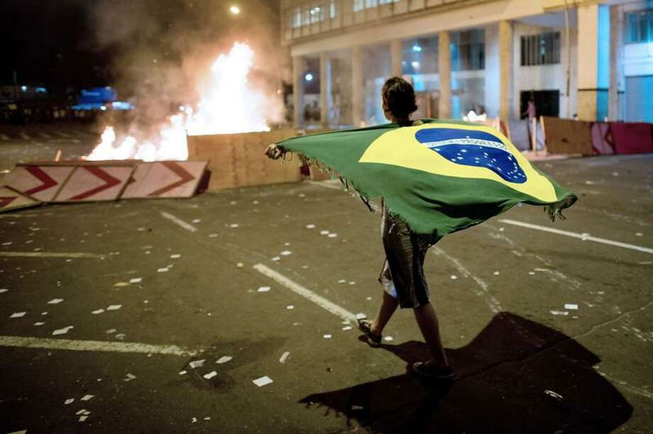 A demonstrator walks with a Brazilian flag late on June 19, 2013 in the center of Niteroi, 10 kms from Rio de Janeiro. Protesters battled police late on June 19, even after Brazil's two biggest cities rolled back the transit fare hikes that triggered two weeks of nationwide protests.  The fare rollback in Sao Paulo and Rio de Janeiro marked a major victory for the protests, which are the biggest Brazil has seen in two decades.   CHRISTOPHE SIMON/AFP/Getty Images Photo: AFP/Getty Images / AFP