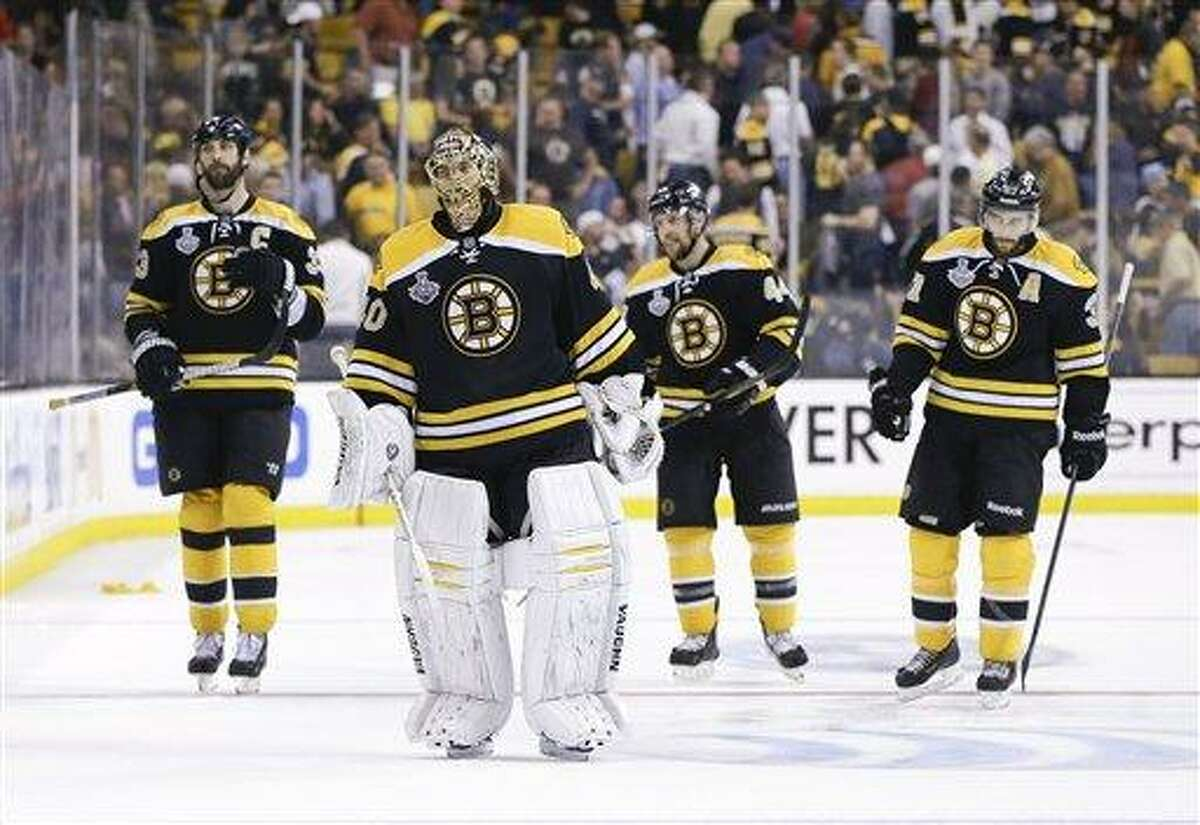 Boston Bruins defenseman Zdeno Chara (33), of Slovakia, Boston Bruins goalie Tuukka Rask (40), of Finland, Boston Bruins defenseman Dennis Seidenberg (44), of Germany, and Boston Bruins center Patrice Bergeron (37) leave the ice after their 6-5 loss to the Chicago Blackhawks during the first overtime period in Game 4 of the NHL hockey Stanley Cup Finals, Wednesday, June 19, 2013, in Boston. Chicago won 6-5.(AP Photo/Elise Amendola)