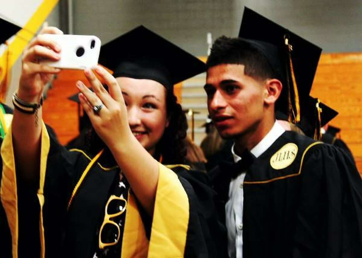 Left, Asia Cowby and right, Andres Navarro take pictures before the Jonathon Law graduation ceremony in Milford on 06/20/2013. Nicole Dellolio/ For the Register