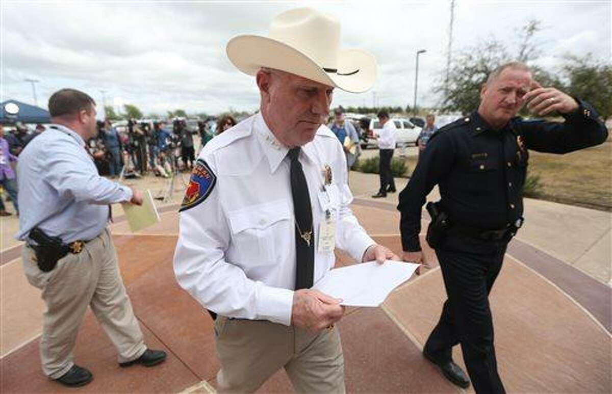 Kaufman County Sheriff David Byrnes, center, walks away after a news conference in Kaufman, Texas, on Sunday March 31, 2013. On Saturday, Kaufman County District Attorney Mike McLelland and his wife, Cynthia, were murdered in their home. (AP Photo/Mike Fuentes)