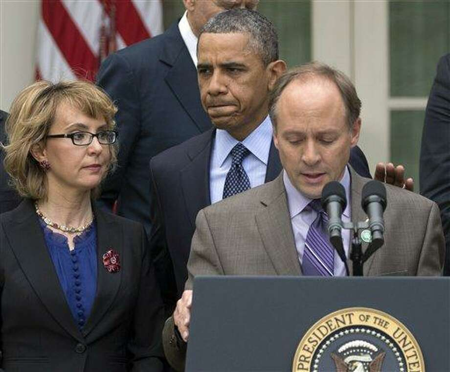 President Barack Obama arrives to participate in a news conference in the Rose Garden of the White House, Wednesday, April 17, 2013, in Washington, about measures to reduce gun violence. With tObama is former Rep. Gabby Giffords, left, and Mark Barden, the father of Newtown shooting victim Daniel.  (AP Photo/Carolyn Kaster) Photo: AP / AP