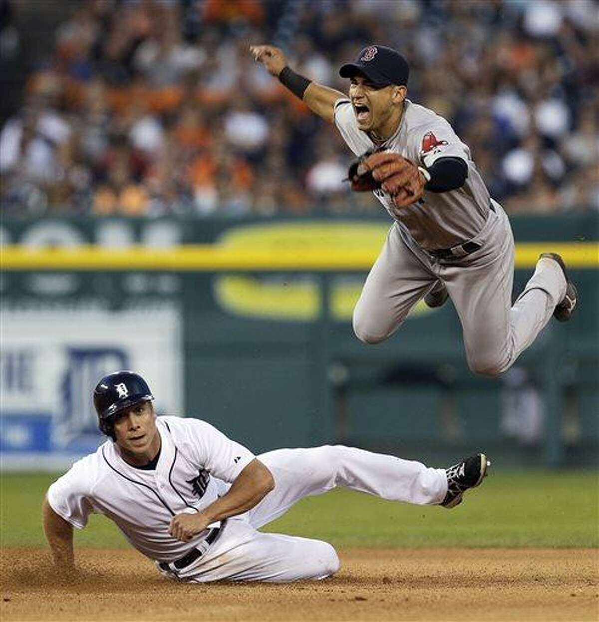 Boston Red Sox's Jose Iglesias jumps after Detroit Tigers' Andy Dirks, bottom, slides to break up the throw to first base on a Brayan Pena fielders choice in the seventh inning of a baseball game in Detroit, Thursday, June 20, 2013. Pena was safe at first base. (AP Photo/Paul Sancya)