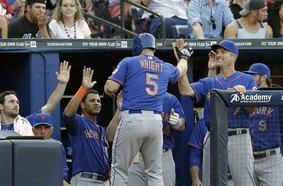 New York Mets' David Wright (5) is greeted at the dugout after hitting a solo home run in the fourth inning of a baseball game against the Atlanta Braves, Thursday, June 20, 2013 in Atlanta. The home run was Wright's second of the game. (AP Photo/John Bazemore) Photo: AP / AP