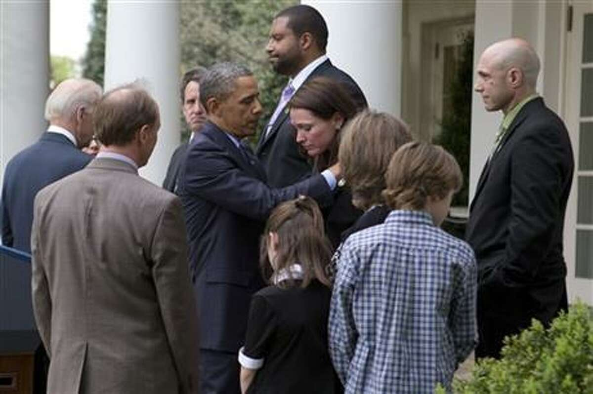 President Barack Obama hugs Nicole Hockley, whose son Dylan was killed in the shooting at Newtown, while surrounded by other Newtown families after speaking about the Rose Garden about the failure of gun legislation to pass in Congress, in the Rose Garden at the White House in Washington, Wednesday, April 17, 2013. Watching in the foreground are Mark and Jackie Barden and their children Natalie and James, along with Jeremy Richman, right, Jimmy Greene, back center, and Neil Heslin, back left facing camera. (AP Photo/Jacquelyn Martin)