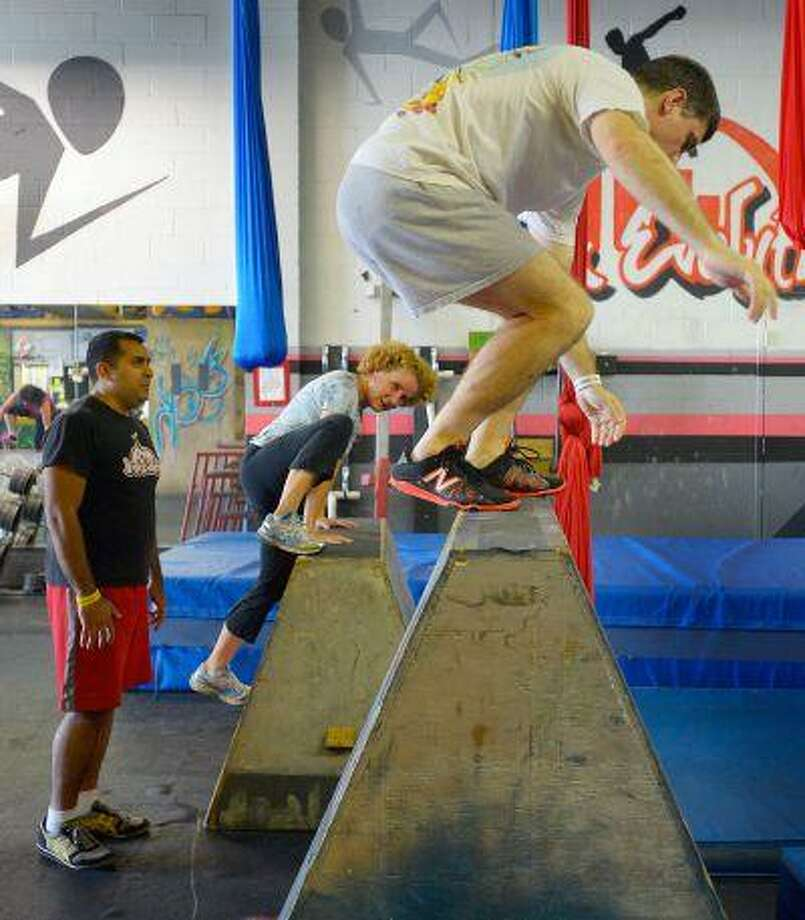 """Instructor Salil Maniktahla, left, observes Kathrin Breitt Brown, center, and George Brown, right, jump onto obstacles as they take part in a """"Parkour"""" class at Urban Evolutions in Alexandria, Va. (Washington Post/John McDonnell)"""