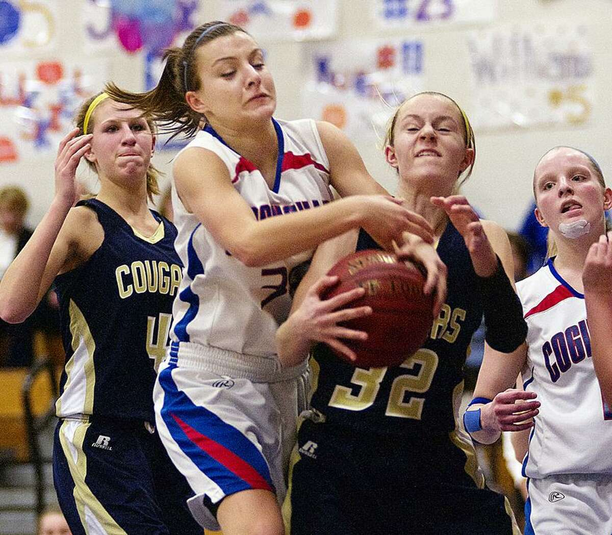 Catherine Avalone/The Middletown Press Coginchaug senior Jessica Solomon battles H-K sophomore Halie Serbent for a rebound. At left is Kiley Anderson (4) and junior forwardMorgan Kuehnle at right. The H-K Cougars came from behind to defeat the Coginchaug Blue Devils 43-39.
