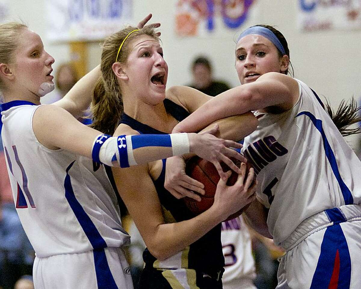 Catherine Avalone/The Middletown PressH-K junior center/forward Kiley Anderson battles Coginchaug junior forward Morgan Kuehnle and junior guard Liv Corazzini for a rebound. The H-K Cougars came from behind to defeat the Coginchaug Blue Devils 43-39.