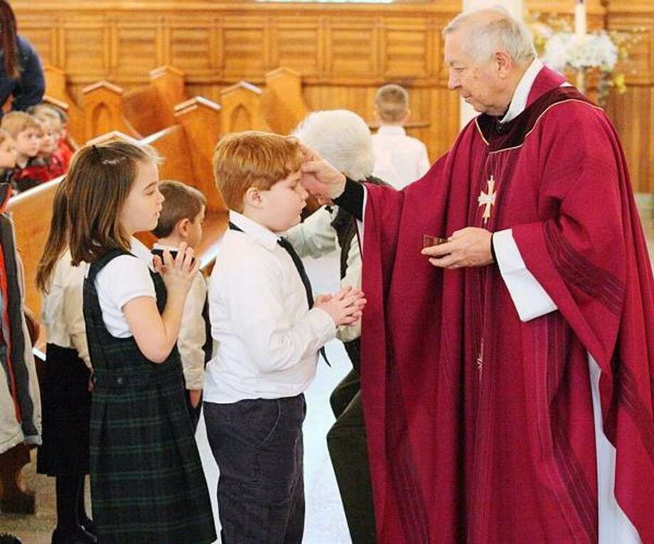 JOHN HAEGER @oneidaphoto on Twitter/Oneida Daily Dispatch Rev. Richard Kapral places ashes on the forehead of St. Patrick's Elementary School third grader Randy Williamson during an Ash Wednesday Service at St. Patrick's Church in Oneida on Wednedsay, Feb. 13, 2013. Photo: Oneida Daily Dispatch / Oneida Daily Dispatch