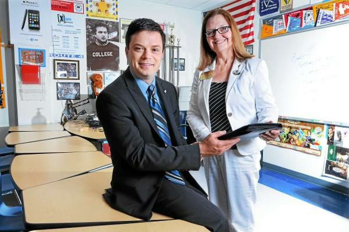Catherine Avalone/The Middletown Press Kathy Randall, Connecticut Consortium Liaison Director presents Dave Reynolds, the Coordinator of Career & Technical Education and DECA Advisor at Middletown High School with a Service Award from Capitol Region Education Council (CREC) Thursday afternoon for five years of continous online teaching.