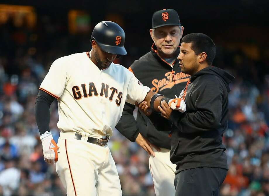 Assistant athletic trainer Eric Ortega and manager Bruce Bochy look at Eduardo Nunez #10 of the San Francisco Giants after he was hit by a pitch in the third inning against the Pittsburgh Pirates at AT&T Park on July 25, 2017 in San Francisco, California. Photo: Ezra Shaw, Getty Images