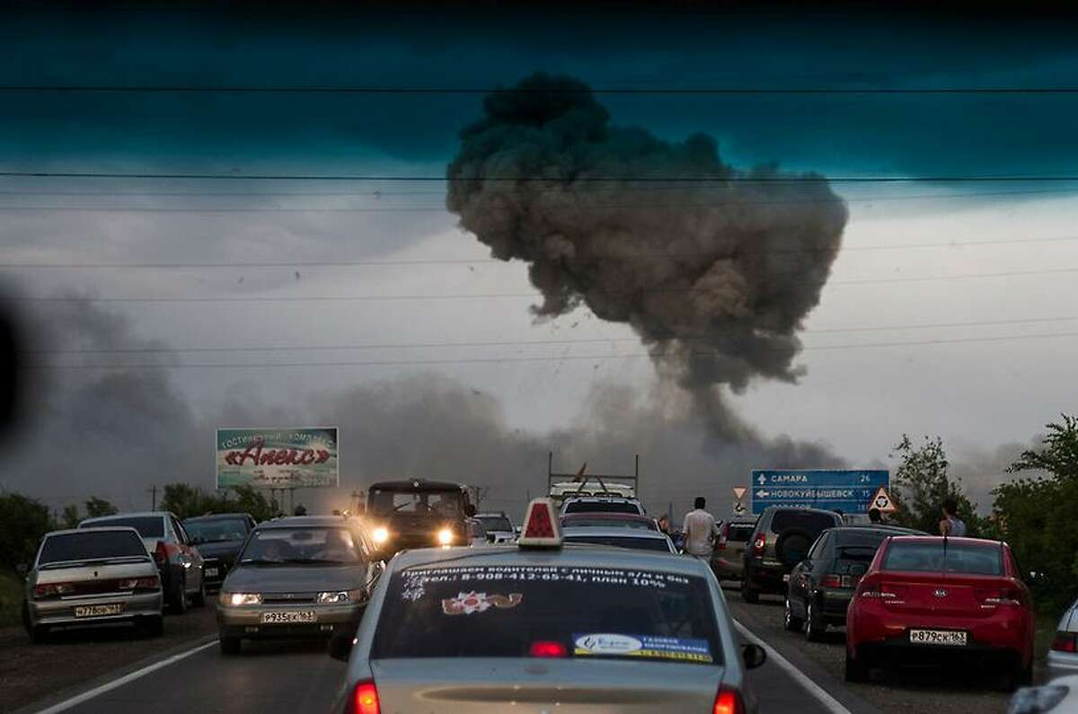 In this photo taken late Tuesday, June 18, 2013 a traffic jam forms on a highway blocked because of a fire at a military depot near Chapaevsk in the Samara region of southern Russia. Exploding shells set off a fire that was triggering explosions Wednesday at a military depot in southern Russia, injuring about 30 people and causing the evacuation of more than 6,000 from a nearby village, investigators and emergency workers said. (AP Photo/Anatoly Bazhukov)