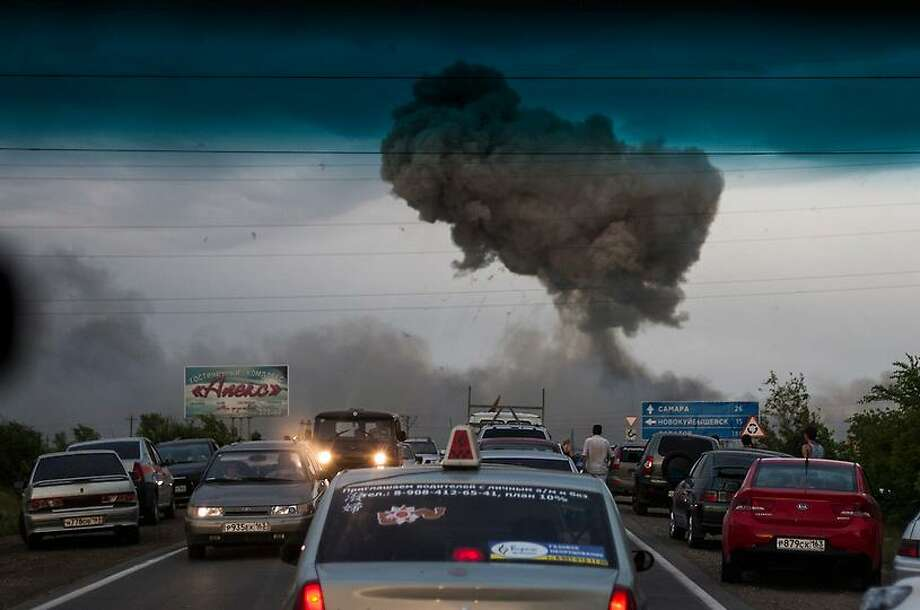 In this photo taken late Tuesday, June 18, 2013 a traffic jam forms on a highway blocked because of a fire at a military depot near Chapaevsk in the Samara region of southern Russia. Exploding shells set off a fire that was triggering explosions Wednesday at a military depot in southern Russia, injuring about 30 people and causing the evacuation of more than 6,000 from a nearby village, investigators and emergency workers said.  (AP Photo/Anatoly Bazhukov) Photo: ASSOCIATED PRESS / AP2013
