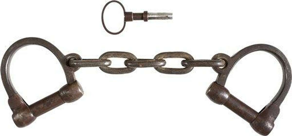 This June 17, 2013 provided by Heritage Auctions, shows the pair of leg irons, or shackles, believed to be those used on John Brown during his incarceration at the Charlestown, W.Va., jail following his arrest during the raid at Harper's Ferry W.Va. John Brown's capture of the Federal Arsenal at Harper's Ferry on Oct. 17, 1859 as part of a failed attempt to incite a slave uprising is seen by most historians as the spark that ignited the Civil War. They have been passed down in the family of John Boling, of Idaho, for six generations, after being obtained by a decedent shortly after Brown's execution. They are expected to bring more than $10,000 when they come up for auction on June 22, 2013. (AP Photo/Heritage Auctions)