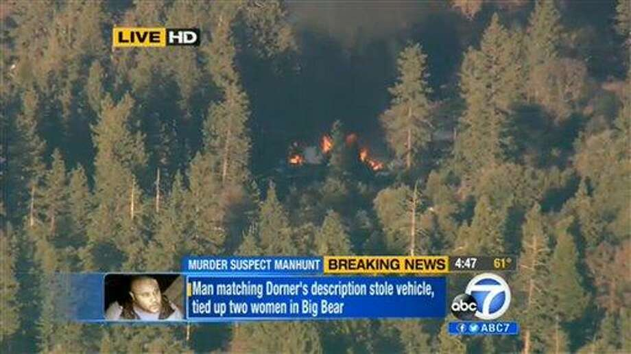 In this image taken from video provided by KABC-TV, the cabin in Big Bear, Calif. where ex-Los Angeles police officer Christopher Dorner is believed to be barricaded inside is in flames Tuesday, Feb. 12, 2013. (AP Photo/KABC-TV) Photo: AP / KABC-TV