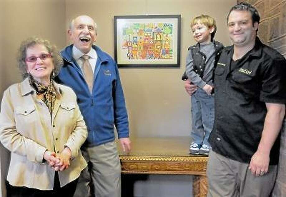 Catherine Avalone/The Middletown Press Christine Firth of Wallingford donated a signed and numbered lithograph illustrated by Ruth Zarfati, an Israeli children's illustrator to the Russell Library. Firth met with Vince Juliano, assistant director at Russell Library and Dmitri D'Alessandro, owner of Middletown Framing who donated the materials and his time to frame the artwork.  Nikolai D'Alessandro,3 came to help hang the illustration on the library wall with his father.  . / TheMiddletownPress
