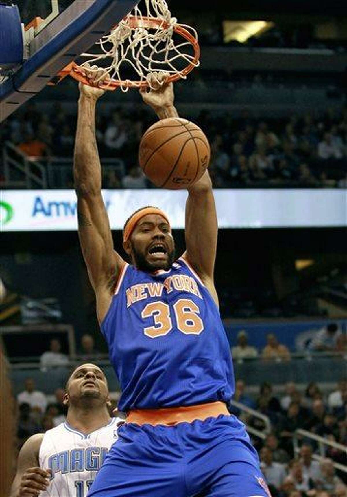 FILE - In this Nov. 13, 2012 file photo, New York Knicks' Rasheed Wallace (36) dunks the ball in front of Orlando Magic's Glen Davis, left, during the first half of an NBA basketball game in Orlando, Fla. Wallace has retired again from the NBA after he was unable to recover from a left foot injury. The Knicks say in a statement that because of his injury Wallace