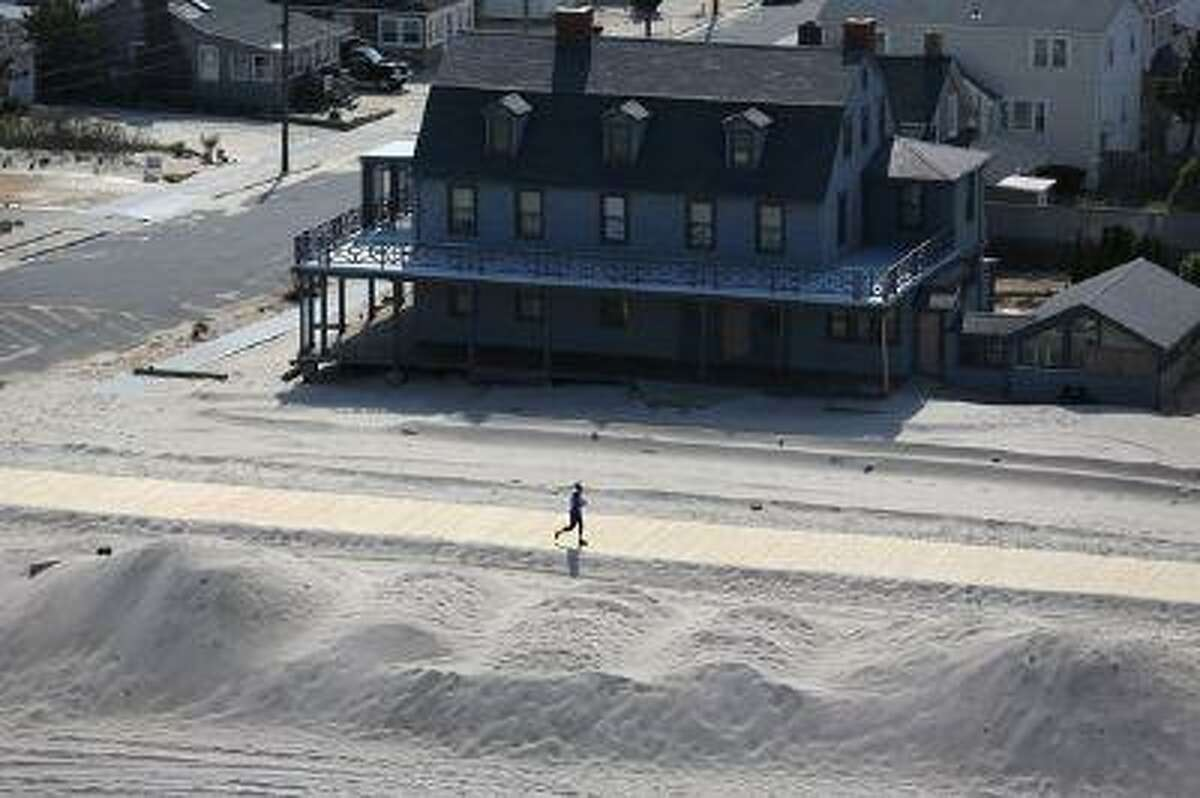A resident jogs along a new stretch of boardwalk and restored beach more than six months after Superstorm Sandy in May 2013 in New Jersey. (John Moore/Getty Images)