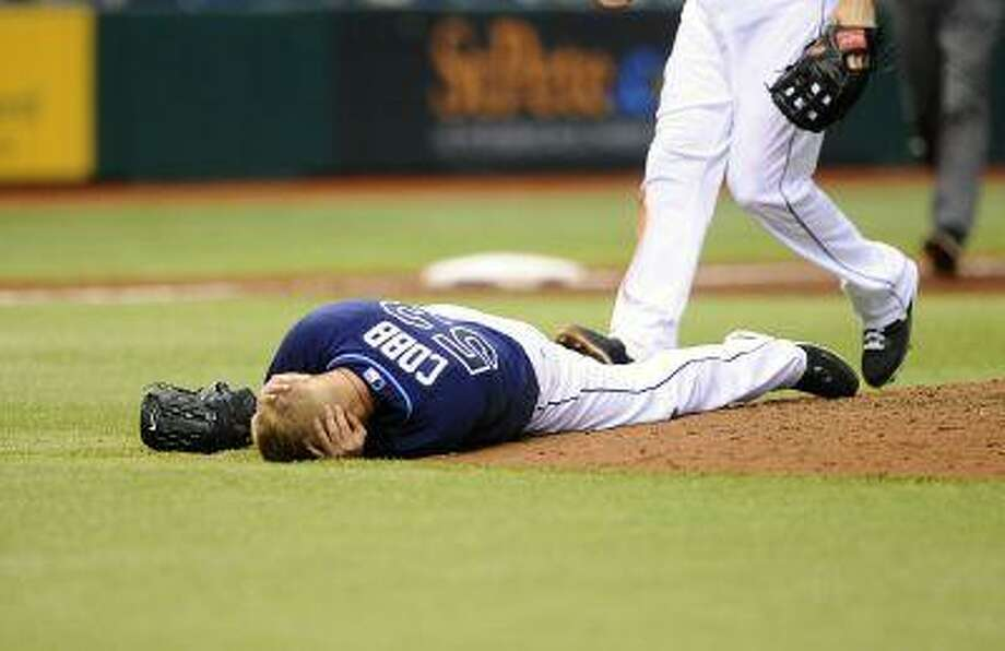 Tampa Bay Rays starting pitcher Alex Cobb grabs his head and lies on the pitcher's mound after being hit by a line drive by Kansas City Royals' Eric Hosmer during the fifth inning of a baseball game Saturday, June 15, 2013, in St. Petersburg, Fla. Cobb was taken off the field on a stretcher. Photo: ASSOCIATED PRESS / AP2013