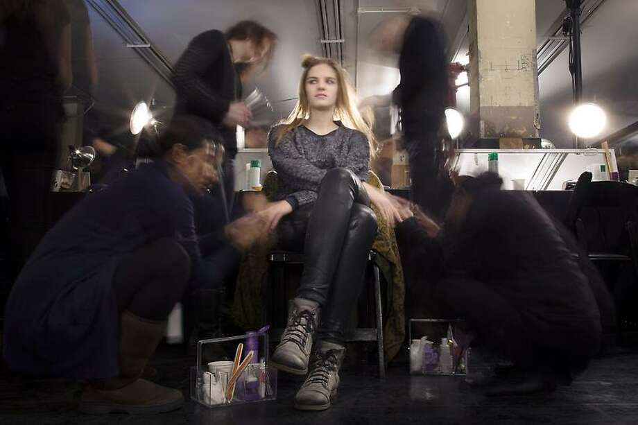 In this photo made with a long exposure, a model is prepared backstage before the Theyskens' Theory Fall 2013 collection is shown during Fashion Week, Monday, Feb. 11, 2013, in New York. (AP Photo/John Minchillo) Photo: ASSOCIATED PRESS / AP2013