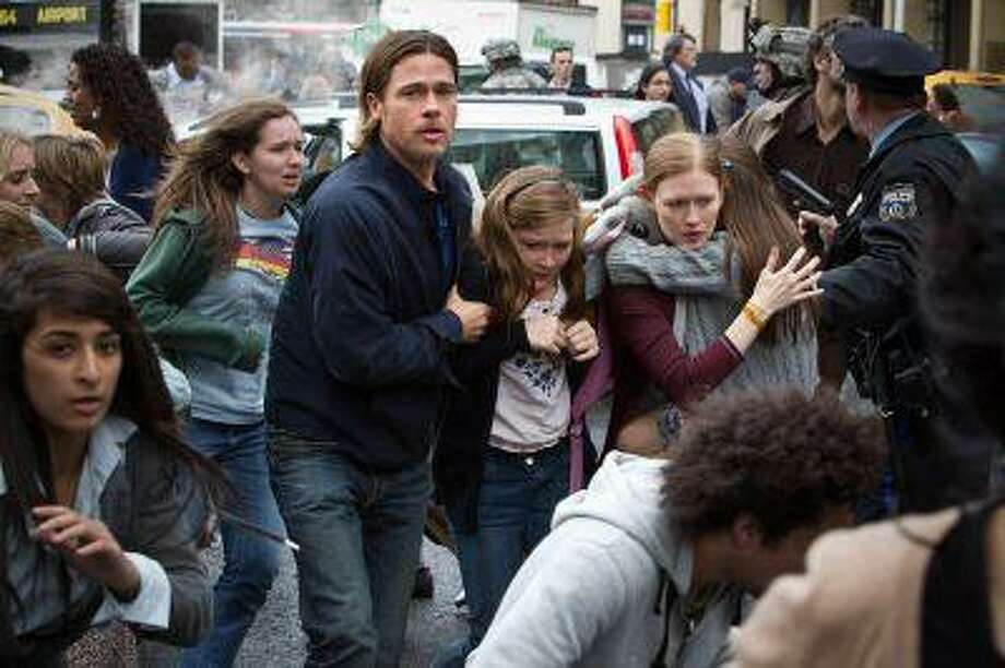 """This publicity image released by Paramount Pictures shows, from center left, Brad Pitt as Gerry Lane, Abigail Hargrove as Rachel Lane, and Mireille Enos as Karin Lanein a scene from """"World War Z."""" (AP Photo/Paramount Pictures, Jaap Buitendijk) Photo: AP / Paramount Pictures"""